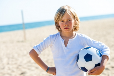 casualness: Portrait of unhappy boy with soccer ball on beach.