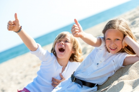 Two kids on beach showing thumbs up symbol together. photo