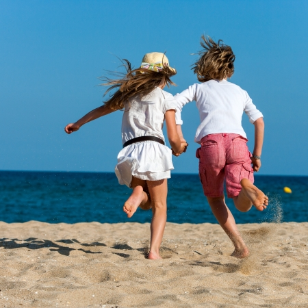 dynamic activity: Two kids holding hands running towards sea.