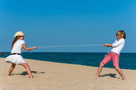 Boy and girl pulling the rope on the beach. photo