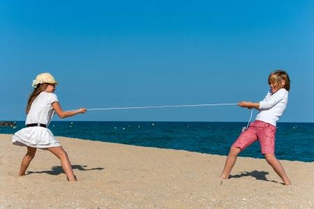 Jungen und Mädchen ziehen das Seil am Strand.