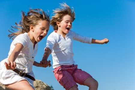 Two kids shouting and jumping together outdoors. photo