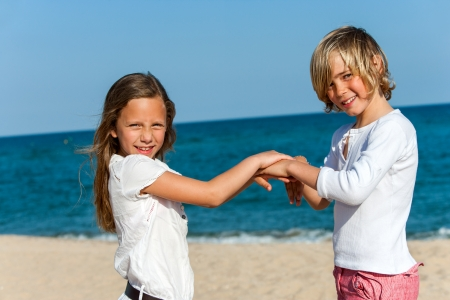 Portrait of two children playing hand game on beach. photo