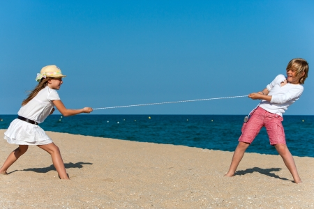 Two kids having a tug war on the beach. photo