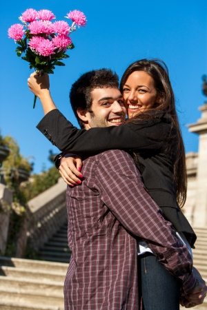 Close up portrait of young couple embracing outdoors with flower bouquet. photo