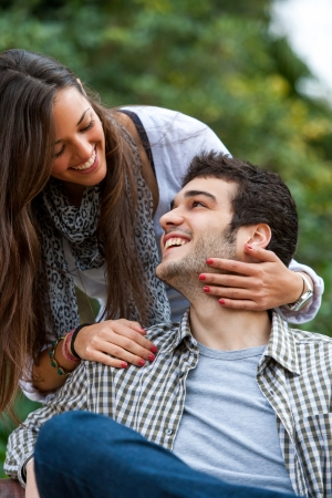Portrait of young couple smiling at each other in park. photo
