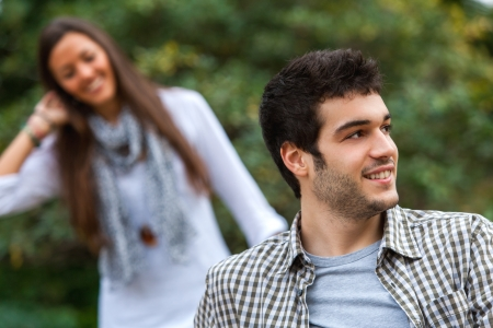 Close up portrait of young man looking aside with girlfriend in background. photo