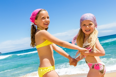 beach wear: Two kids enjoying a day at the beach together.