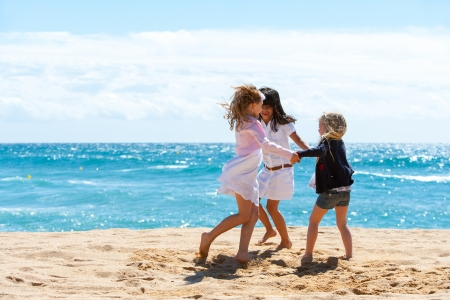 kids playing beach: Three young girlfriends playing game on beach. Stock Photo