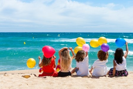 Young kids holding color balloons sitting on beach.  Imagens