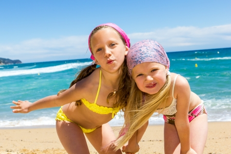 kid  playing: Close up portrait of two girlfriends in swimwear on beach.