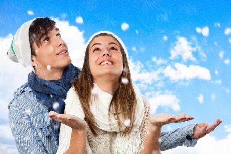 boinas: Primer plano retrato de una pareja de invierno jugando con los copos de nieve.