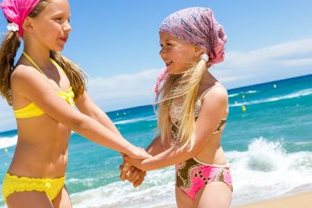children holding hands: Portrait of two happy kids in swim wear at sea