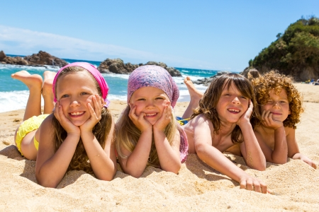 kids playing beach: Portrait of children laying on sand at beach  Stock Photo