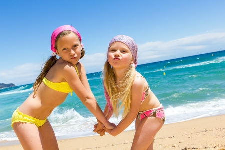 sister: Portrait of two youngsters with funny face expression on beach  Stock Photo