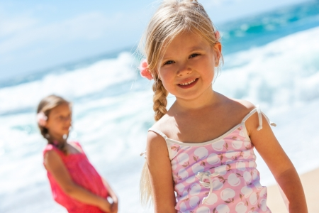 beach blond hair: Close up portrait of cute girl on beach with friend in background  Stock Photo