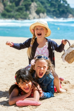summer holiday: Close up portrait of cute threesome making human pile on beach  Stock Photo