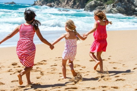 Three young girlfriends running on beach holding hands  photo
