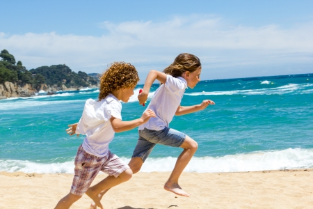 dynamic activity: Two boys having a race on sunny beach  Stock Photo
