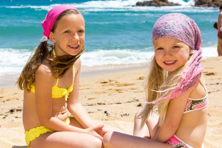 beach wear: Portrait of two kids in swimwear sitting next to sea