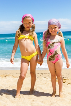 Full length Portrait of two girls in swimwear standing on beach  photo