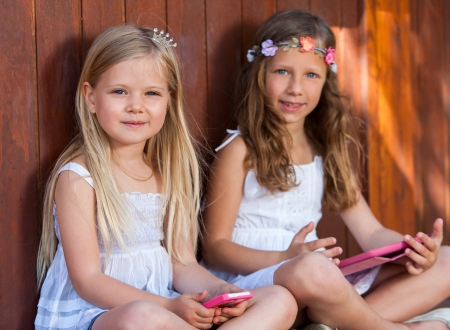 pre teen girl: Close up portrait of two kids with tablet and smart phone outdoors. Stock Photo