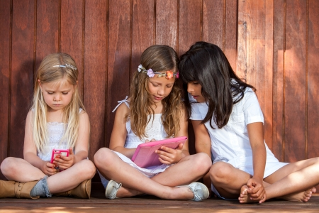 threesome: Close up portrait of three kids socializing with tablet and smart phone outdoors. Stock Photo