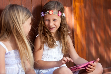 pre teen girls: Portrait of two cute kids playing with digital tablet outdoors.