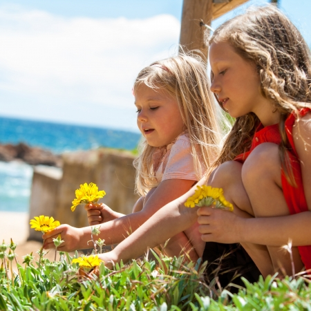 preteens beach: Portrait of two girlfriends picking flowers at seaside. Stock Photo