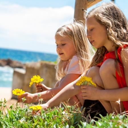 mädchen: Portrait von zwei Freundinnen Blumen pflücken am Meer.