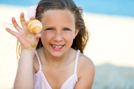 Close up portrait of cute girl showing seashell outdoors. photo
