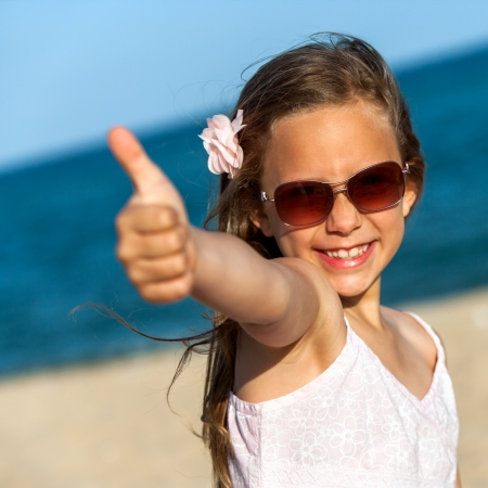 contentedness: Portrait of happy girl showing thumbs up on beach.