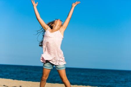 salto largo: Feliz chica joven que levanta los brazos en la playa.