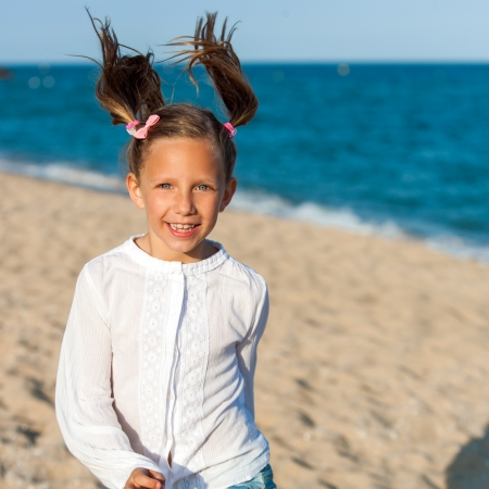 ponytails: Portrait of happy girl with ponytails at seaside.