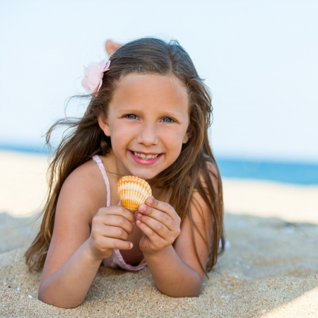 Close up portrait of smiling girl with shell on beach. photo