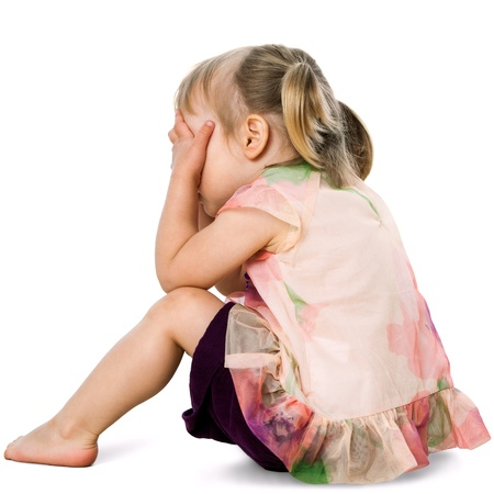 Portrait of upset little girl hiding face behind hands.Isolated on white. photo