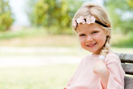 jolie petite fille: Portrait de mignonne petite fille assise sur un banc en bois à l'extérieur.