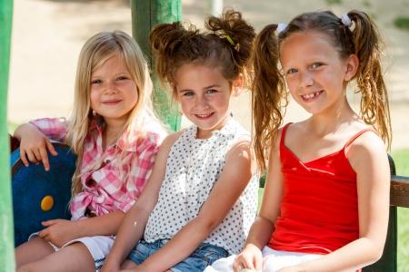 trio: Cerrar un retrato de grupo de tres amigas que se sientan junto en el parque. Foto de archivo