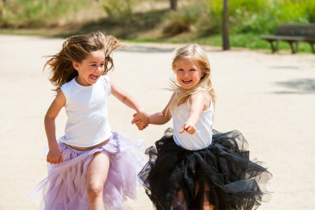 kids holding hands: Two girl friends running together holding hands in park.