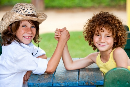 Two boys having arm wrestle in park. photo