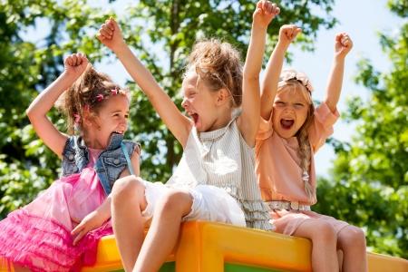 riendo: Conjunto De Tres amigos de la chica levantando las manos y gritando en el parque. Foto de archivo