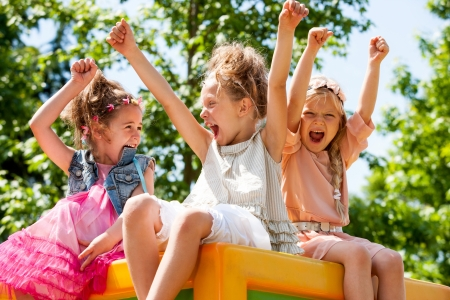 kid sitting: Threesome girl friends raising hands together and shouting in park.