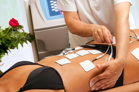 Therapist hands attaching anti aging electrodes on womans body.  Stock Photo