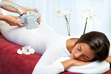 Therapist applying anti cellulite lipomassage on womans body. photo