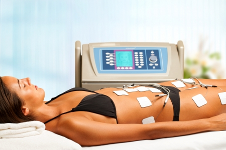 liposuction: Young woman having electrical lymphatic drainage in spa.