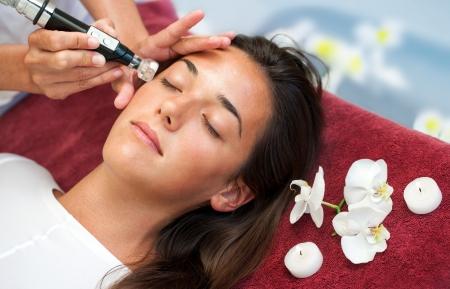 mujer celulitis: Terapeuta haciendo contra el envejecimiento de la infusión de humedad facial en mujer. Foto de archivo