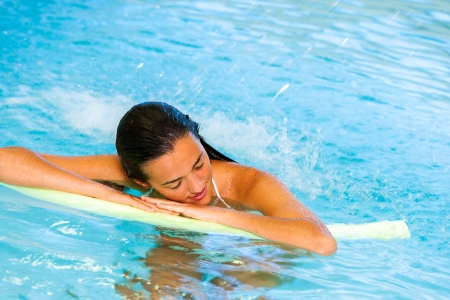 Attractive young woman relaxing under cascade in spa pool. photo