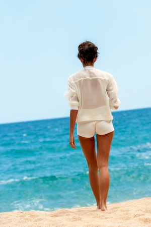giving back: Elegant brunette in white outfit walking towards blue sea. Stock Photo