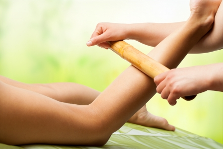 green bamboo: Close up of female hands doing bamboo massage on womans legs. Stock Photo