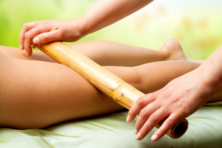 beauty therapist: Close up of therapist hands massaging female legs with bamboo stick. Stock Photo